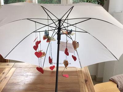 Weißer Regenschirm mit Herzen und Geldscheinen
