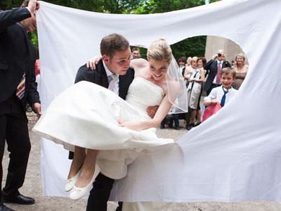 Bräutigam trägt Braut durchs Bettlaken