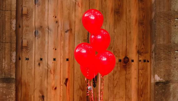 Rote Luftballons vor Holzwand